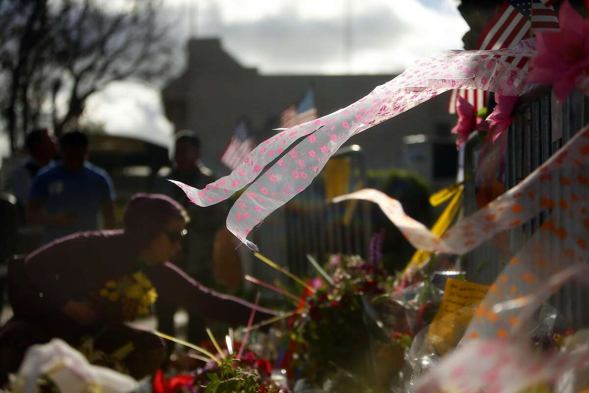 As the wind blows through a Fruitvale Avenue memorial, Tiffany Snow of Oakland places flowers in memory of her friend Griffin Madden who died in the Ghost Ship warehouse fire in Oakland, Calif., on Tuesday, December 6, 2016.