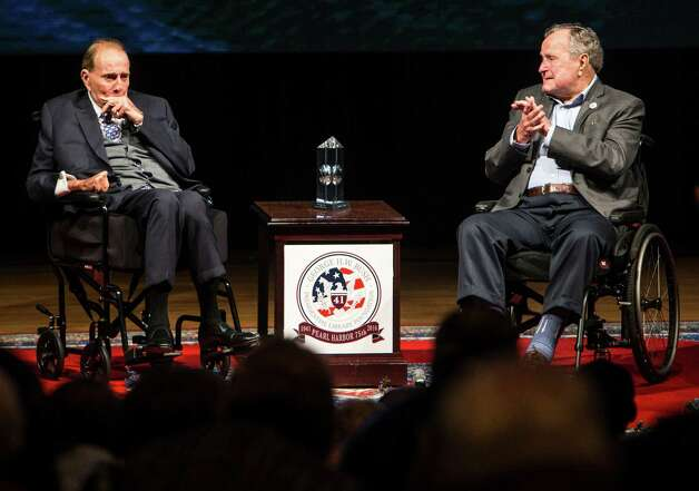 Former Sen. Bob Dole, R-Kansas, left, is presented the George Bush Award for Public Service by former President Bush on Wednesday following the 75th anniversary ceremony of the attack on Pearl Harbor. Photo: Brett Coomer, Staff / © 2016 Houston Chronicle