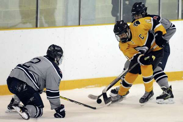 Brunswick's Christian LeSueur (11) battles for the puck against Kent's Nick Smith and Will Robertson in the first period at Hartong Rink in Greenwich on Wednesday. Brunswick defeated Kent 3-0.
