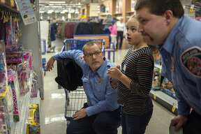 City of Midland firefighters Tony Lelo, left, and Max Kopplin help 8-year-old Lia Dice pick out a Christmas gift for her sister at Meijer Wednesday evening. Approximately 20 children went shopping with members of the Midland County Sheriff's Office, City of Midland Police, City of Midland Fire and Mid-Michigan Medical Emergency staff during the annual Shop with a Hero. Each child received a $100 Meijer gift card to spend on whatever they wanted for Christmas.