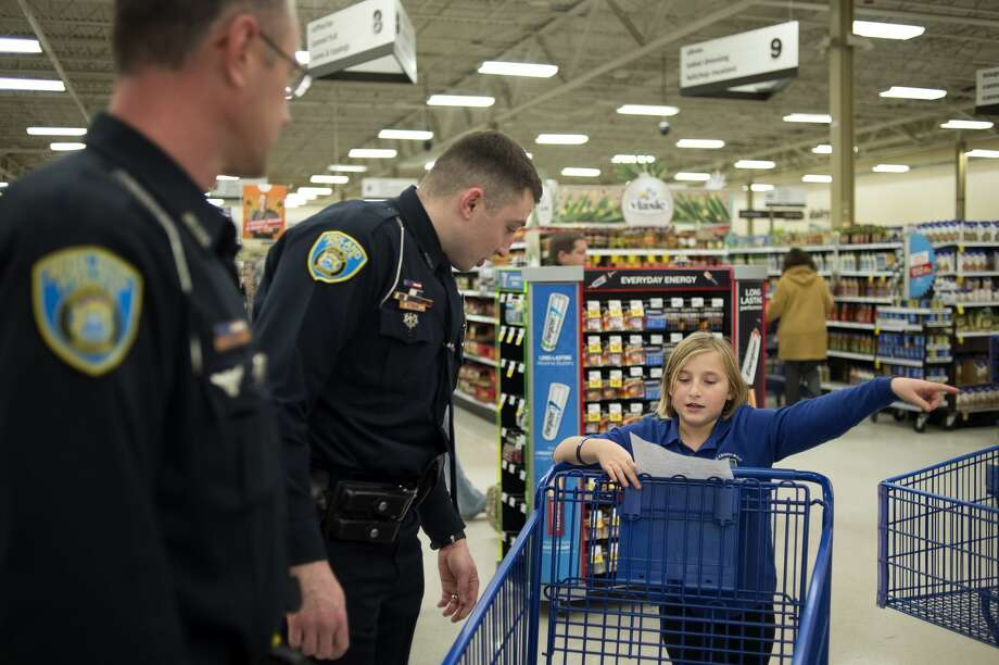 Nine-year-old Danielle Kurzer points the direction she wants to go shopping first to City of Midland police officers Scott Coyle, left, and Travis Toth at Meijer Wednesday evening. Approximately 20 children went shopping with members of the Midland County Sheriff's Office, City of Midland Police, City of Midland Fire and Mid-Michigan Medical Emergency staff during the annual Shop with a Hero. Each child received a $100 Meijer gift card to spend on whatever they wanted for Christmas. Photo: Brittney Lohmiller/Midland Daily News/Brittney Lohmiller