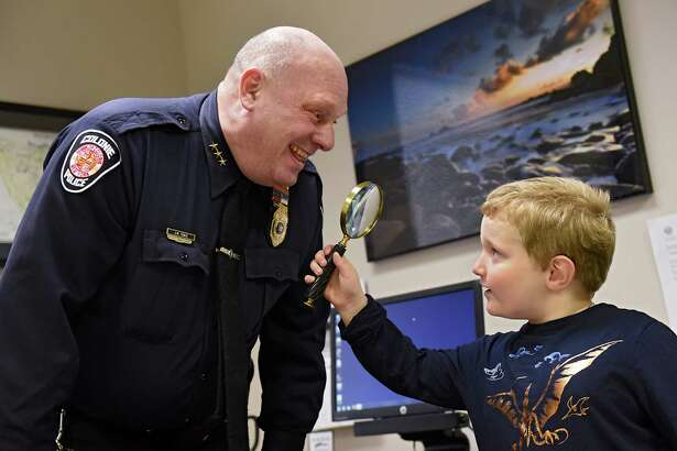 Colonie Police Chief Jonathan Teale smiles as James Assimon, 6, of Watervliet looks at him through a magnifying glass in his office as James gets a tour of the station on Wednesday, Dec. 7, 2016 in Latham, N.Y. James donated guardian angel pins to police after news of violence against police elsewhere. He had life-saving brain surgery in 2014, has since given out 700-800 pins made by his mom. They started after he told his Mom he wants to make people smile when he grows up.(Lori Van Buren / Times Union)