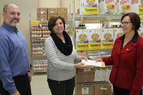 United University Professions UAlbany Chapter delegate Greta Petry, right, presents a $1,010 contribution to St. Vincent de Paul Food Pantry Director Angela Warner from the chapter to fight hunger at the college and in the community. UUP UAlbany Chapter President Bret Benjamin looks on as the donation was made at the Madison Avenue food pantry.  UUP and UAlbany are working together to develop fundraising and volunteer efforts to help the pantry. (Photo by Donald Feldstein)