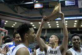 The Elkins Knight's players celebrate their win against the Beaumont Ozen Panthers in high school basketball's 5A Region III finals on Saturday, March 5, 2016 at the Merrell Center.