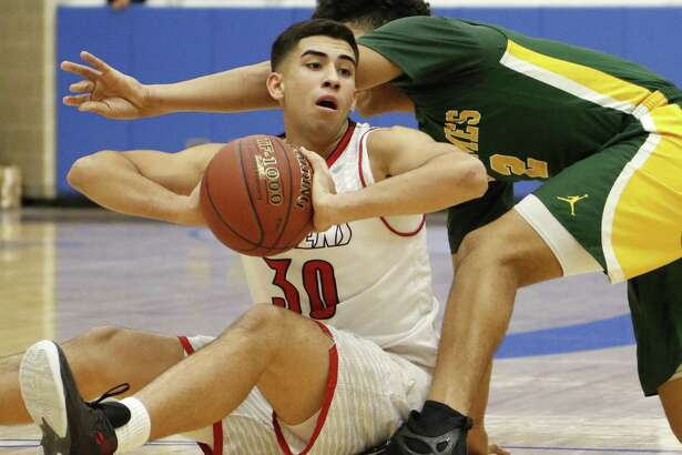 Stevens Jonathan Salazar looks to pass as he is trapped by a Holmes player from the District 28-6A boys basketball opener between Holmes and Stevens at the Northside ISD gymnasium on Wednesday, December 7, 2016.