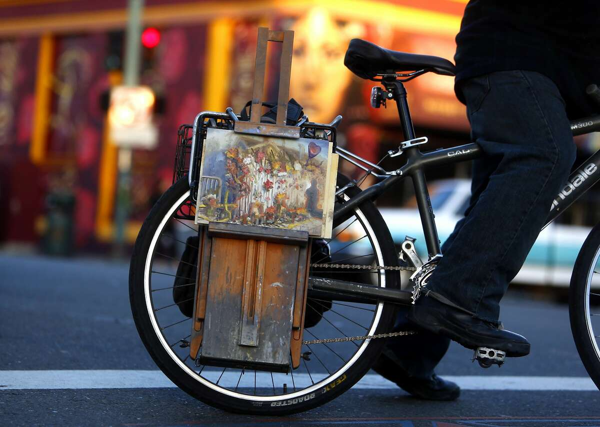 After painting a memorial on E. 12th Street, artist John Paul Marcelo of Oakland rides his bike home n the aftermath of the deadly Ghost Ship warehouse fire in Oakland, Calif., on Tuesday, December 6, 2016.
