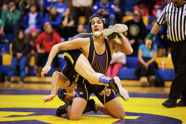 THEOPHIL SYSLO | For the Daily News Midland High School's Matthew Waier wrestles with Bay City Central's Marcos Facundo in a match at Midland High School on Wednesday.