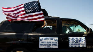 An American flag flies out of the window of a truck headed towards the Donald Trump rally at the Northwest Washington Fair and Event Center in Lynden, Wash. on Saturday, May 8, 2016.