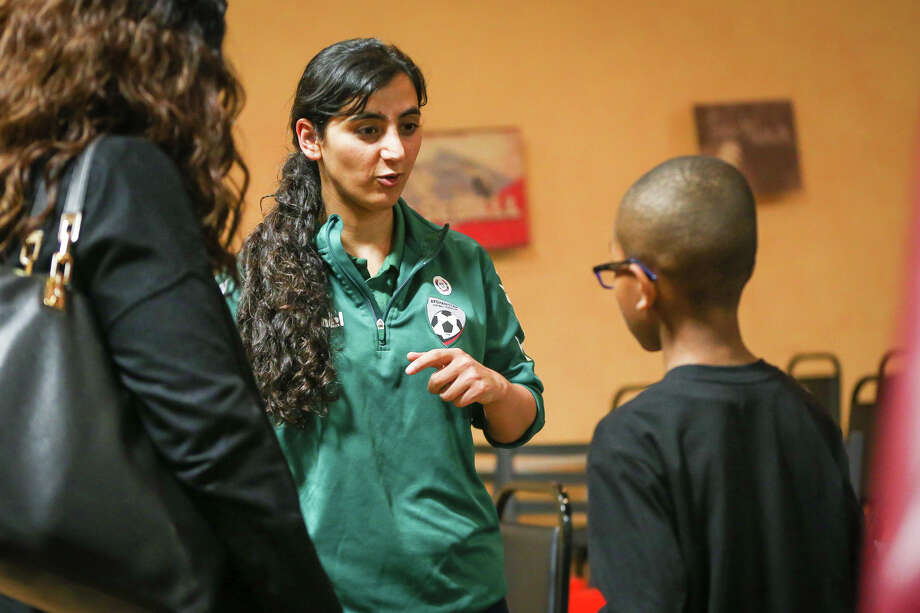 9-year-old Corland Atkins, of The Woodlands, asks guest speaker Khalida Popal, program director for the Afghanistan Women's National Football Team, how she first got interested in soccer as his mother Valerie looks on during the World Human Rights Celebration on Monday, Dec. 5, 2016, at Legends Sports Complex. Khalida now lives in Denmark after she was forced to leave Afghanistan for using soccer as a vehicle for empowering women that suffer from abuse and oppression. Photo: Michael Minasi, Houston Chronicle / © 2016 Houston Chronicle