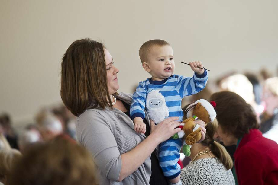 Stephanie Goff helps son and model William Goff, 14 months, show off his outfit at Cancer Services' 25th annual Holiday Luncheon and Style Show fundraiser at the Midland Country Club on Wednesday. Proceeds from the event, which also included a silent auction, will go towards Cancer Services and its Maria Mencia Cancer Caregiver Support Network. Models in the post-lunch fashion show were cancer survivors. Photo: Erin Kirkland/Midland Daily News
