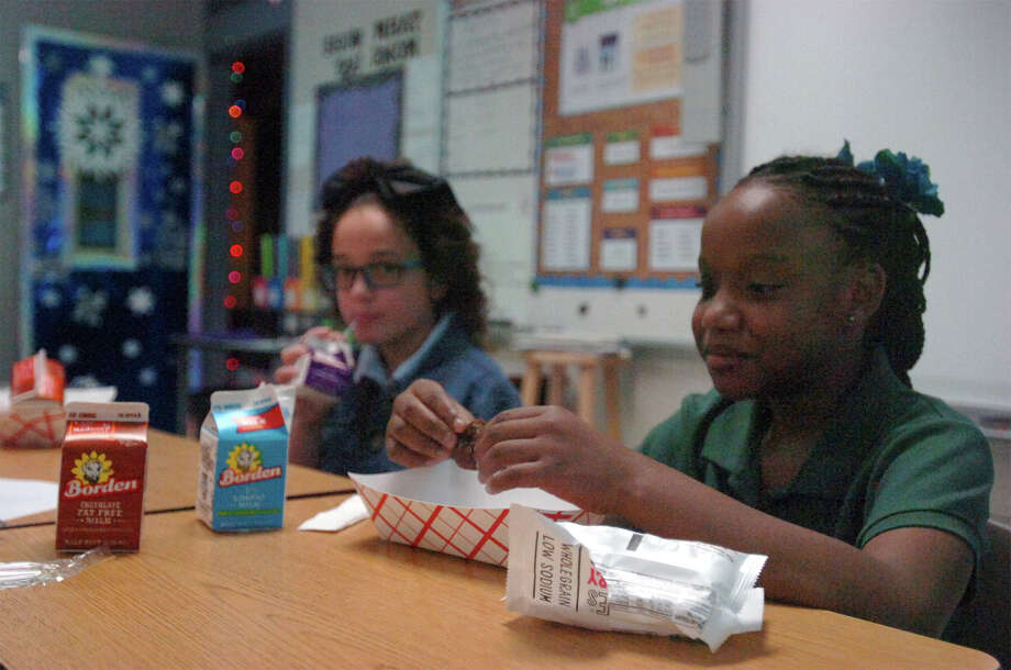 From left, Raylie Evans and Emonie Perkins eat breakfast before class starts at Newton Elementary Tuesday. The school began a new program that feeds all children breakfast in the classroom. Liz Teitz/The Enterprise.
