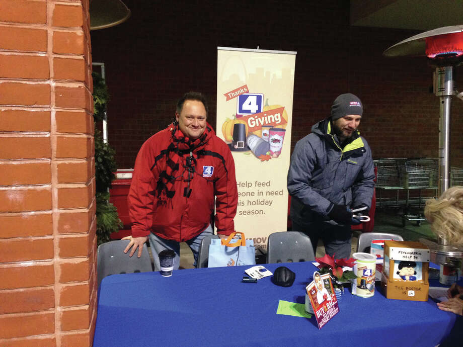 """Braving the cold, KMOV Channel 4 on-air personality Steve Harris, left, and promotions director Brian Spencer man a table outside Dierberg's at Edwardsville Crossing Thursday morning. The two were collecting donations for Operation Food Search as part of Channel 4's Thanks 4 Giving program. The station had representatives at Dierberg's from 6 a.m. to 6 p.m. The first 10 people to donate 10 canned goods received tickets to a performance of """"Finding Neverland"""" at The Fox. Photo by Bill Tucker. Photo: Bill Tucker • Btucker@edwpub.net"""