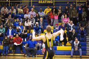 Midland High School's Jessy Hays throws a t-shirt in to the stands after pinning Bay City Central's Douglas Van Paris in a match at Midland High School on Wednesday.  Midland High School is celebrating its 50th anniversary of the Midland wrestling program and giving away t-shirts for every pinned opponent in Wednesday's match.