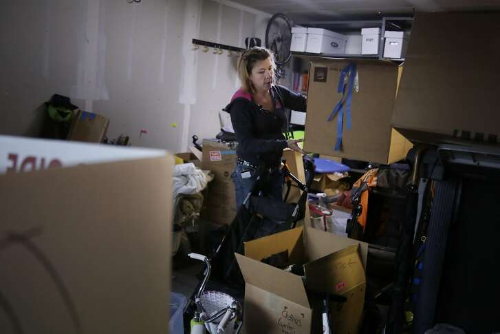 Heather Hawkins of San Francisco moves boxes and goes through belongings in her garage at her home as she prepares for her family's move to Truckee on Wednesday, December 7,  2016 in San Francisco, California.