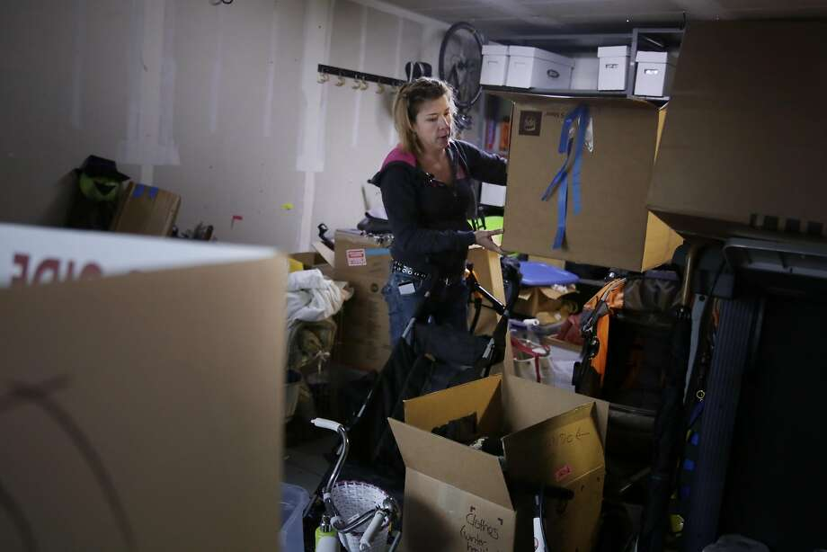 Heather Hawkins goes through items in her family's San Fran cisco garage last month as they prepare for a move to Truckee. Photo: Lea Suzuki, The Chronicle