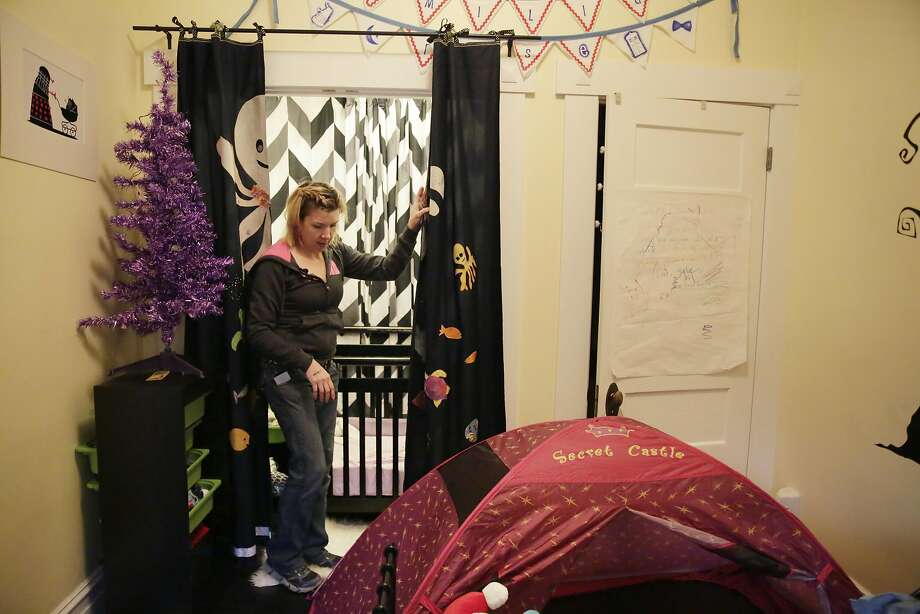 Heather Hawkins draws a curtain across the closet the family had converted into a bedroom for their baby daughter. Photo: Lea Suzuki, The Chronicle