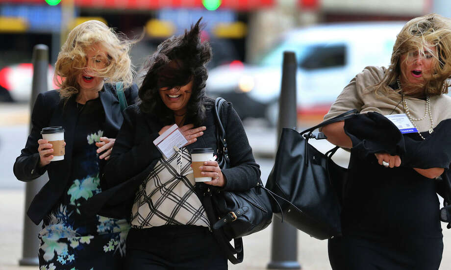 Pedestrians brave high winds Thursday December 8, 2016 while crossing Market street at the intersection of Bowie at the Henry B. Gonzalez Convention Center in downtown San Antonio. The National Weather Service has issued a wind advisory for most of central Texas with gusts as high as 40 mile per hour. Photo: John Davenport, San Antonio Express-News / ©San Antonio Express-News/John Davenport