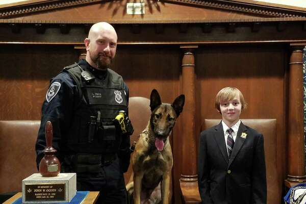Officer Logan Pavia, the department's newest police dog, Loki, and Finn Murphy, 10, who donated all his birthday money to help Stamford Masons raise$2,500to purchase aballistic vest and otherequipmentfor Loki.