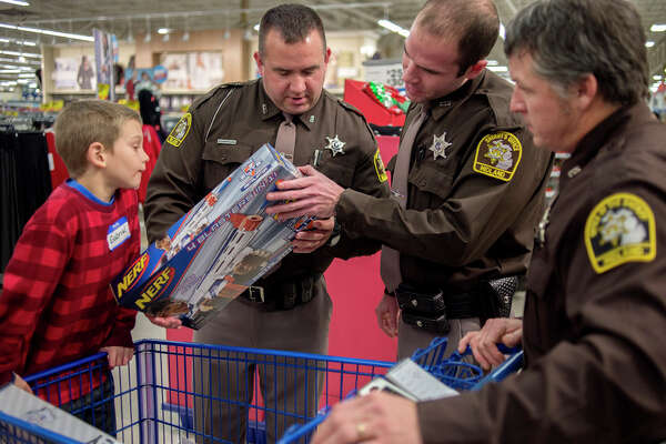 BRITTNEY LOHMILLER | blohmiller@mdn.net From left, 9-year-old Gabriel DiFranco and members of the Midland County Sheriff's Office, Scott McFarland, Mike Butzu and Scott Nohel, look over the Nerf gun DiFranco picked out for a family member at Meijer Wednesday evening. Twenty children went shopping with members of the Midland County Sheriff's Office, Midland Police Department, Midland Fire Department and Mid-Michigan Medical Center-Midland EMS staff during the annual Shop with a Hero. Each child received a $100 Meijer gift card to spend on whatever they wanted for Christmas.