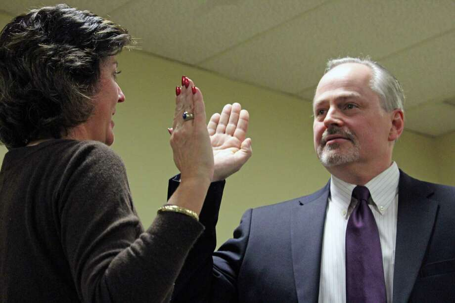 Town Clerk Betsy Browne administers the oath of office to new Selectman Ed Bateson at Wednesday's Board of Selectmen meeting. Fairfield, CT. 12/7/16 Photo: Genevieve Reilly / Hearst Connecticut Media / Fairfield Citizen