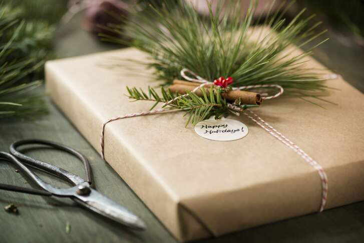 """A box wrapped in kraft paper and baker's twine decorated with a cinnamon stick, long needle pine and hemlock greens. Antique gardening shears and additional greens along side the box.  A round tag wishes the recipient """"Happy Holidays.""""More of this series:"""