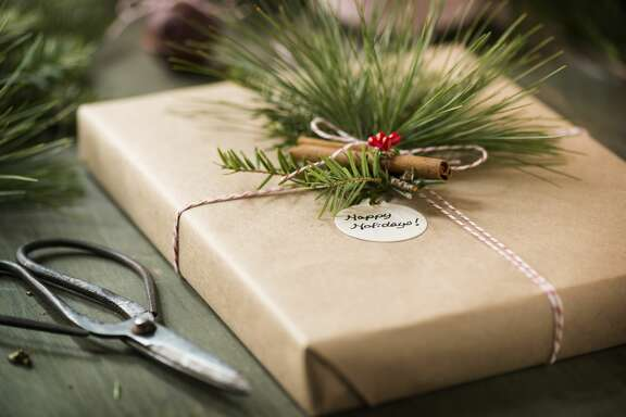 "A box wrapped in kraft paper and baker's twine decorated with a cinnamon stick, long needle pine and hemlock greens. Antique gardening shears and additional greens along side the box.  A round tag wishes the recipient ""Happy Holidays.""More of this series:"