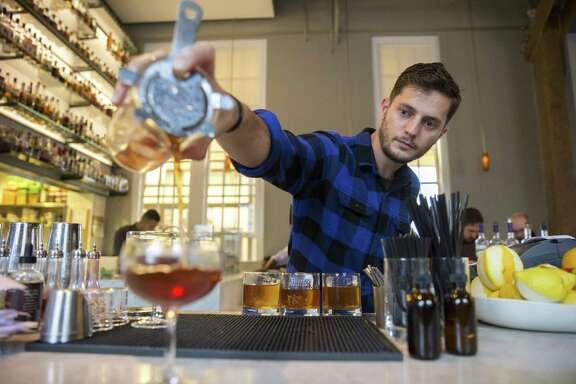 Steve James, a bartender, prepares drinks for customers at Hard Water.