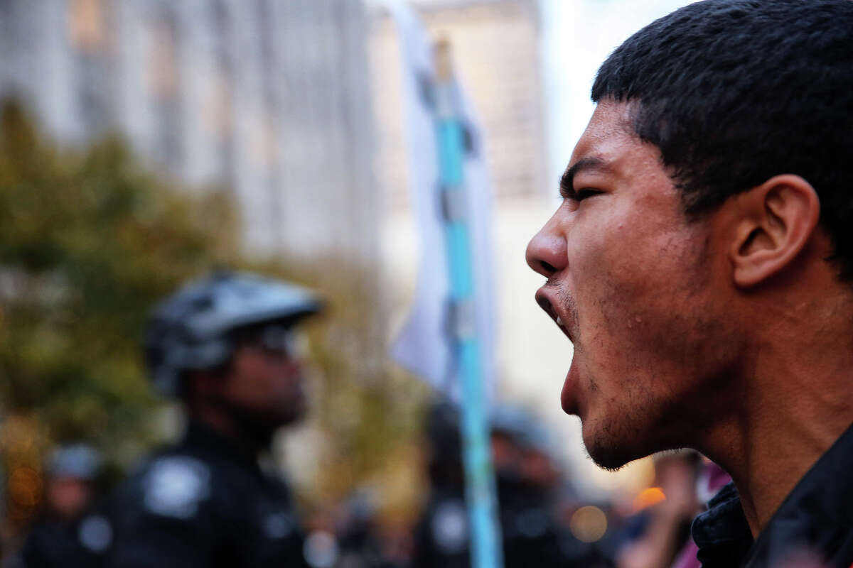 Nova High School student Carlos Ayala, 18, yells at police officers as a small group of high school students, and some others, continue protesting President-elect Donald Trump downtown and have minor clashes with police, Monday, Nov. 14, 2016. (GENNA MARTIN, seattlepi.com)