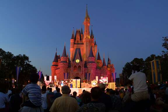 People watch a show on stage in front of Cinderella's castle at Walt Disney World's Magic Kingdom November 11, 2001 in Orlando, Florida. (Photo by Joe Raedle/Getty Images)