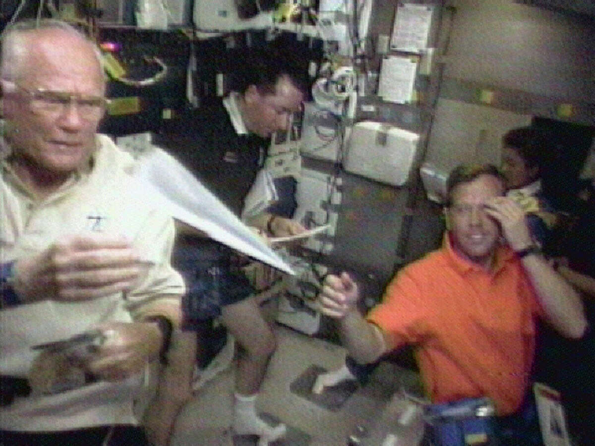 FILE - In this Sunday, Nov. 1, 1998 image made from video, astronaut John Glenn, left, retrieves a paper airplane for pilot Steven Lindsey, foreground right, in the space shuttle Discovery's middeck. Astronaut Stephen Robinson, left, and Japanese astronaut Chiaki Mukai look over paper work in the background. Glenn died Thursday, Dec. 8, 2016, at the age of 95.