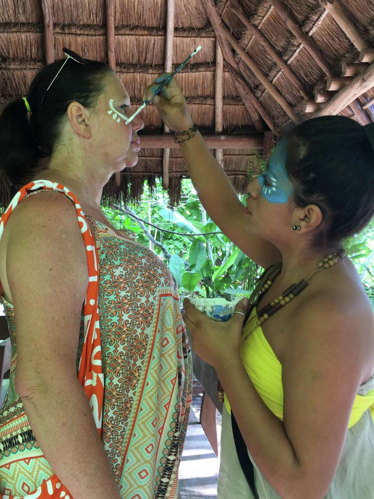 Before entering the recreated ancient Mayan village, guests have their faces painted with natural pigments.