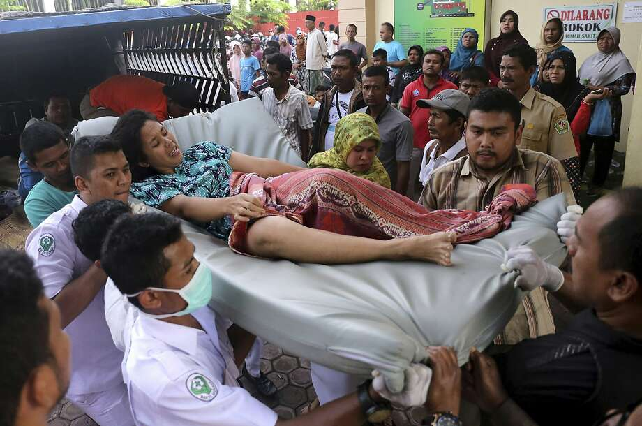 Hospital workers and family members carry a woman injured in an earthquake in Aceh, Indonesia. Wednesday's temblor killed more than 100 people. Photo: Heri Juanda, Associated Press