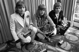 """FILE - This is a Sept. 30, 1972  file photo of  the members of the rock band Emerson, Lake and Palmer,Greg Lake, left Keith Emerson, centre, and Carl Palmer after an award ceremony in London . Greg Lake, the prog-rock pioneer who co-founded King Crimson and Emerson, Lake and Palmer, has died. He was 69. Lake died Wednesday Dec, 7, 2016 after """"a long and stubborn battle with cancer,"""" according to his manager. (PA File via AP)"""