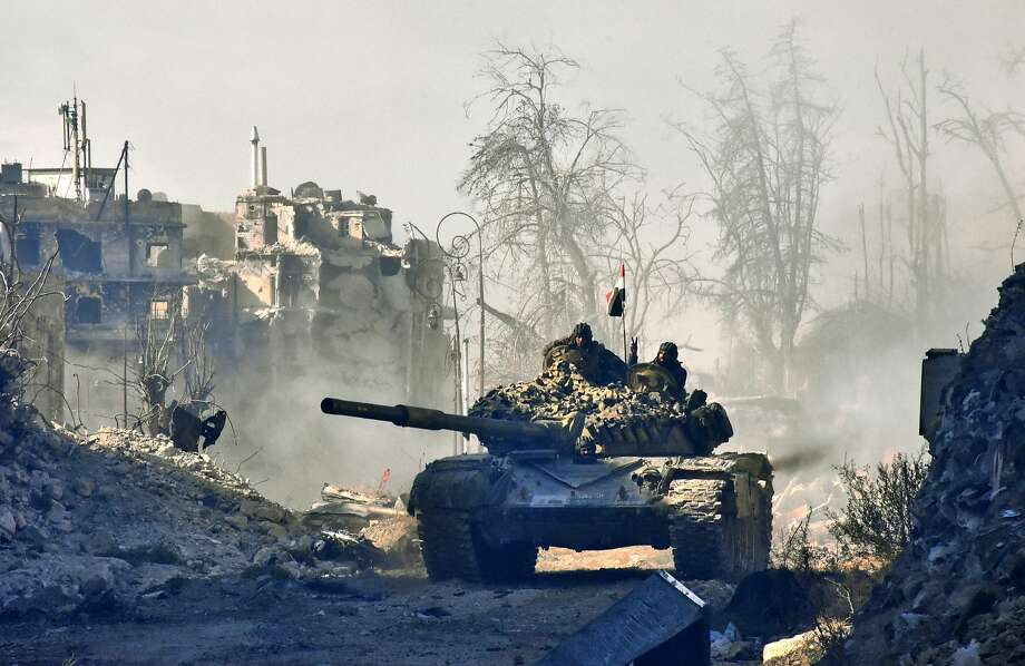 Syrian forces drive a tank through a battle-scarred area of Aleppo. Russia says the army suspended combat in the city to allow for the evacuation of civilians. Photo: GEORGE OURFALIAN, AFP/Getty Images
