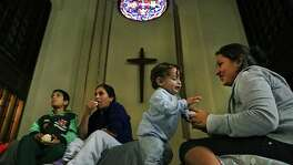 Maria Teresa Quinones, right, plays with her 1 year old son Angel Gael Vanegas from Honduras, as Xiomara Vega Morales, 33 sits with her son Marlon Vega Morales, 8, left, of Guatemala in the sanctuary at the San Antonio Mennonite Church where hundreds of immigrants from Central America have been dropped off by ICE.  Volunteers mentioned they went out to buy blankets and air mattresses, and the last bus dropped off another group at 3 A.M. on Monday, Dec. 5, 2016.