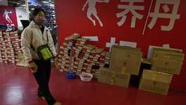 A shopper walks past a Qiaodan Sports retail shop in Beijing. China's highest court ruled in favor of basketball legend Michael Jordan over use of the Chinese rendering by Qiaodan Sports of his Chinese name and trademark.