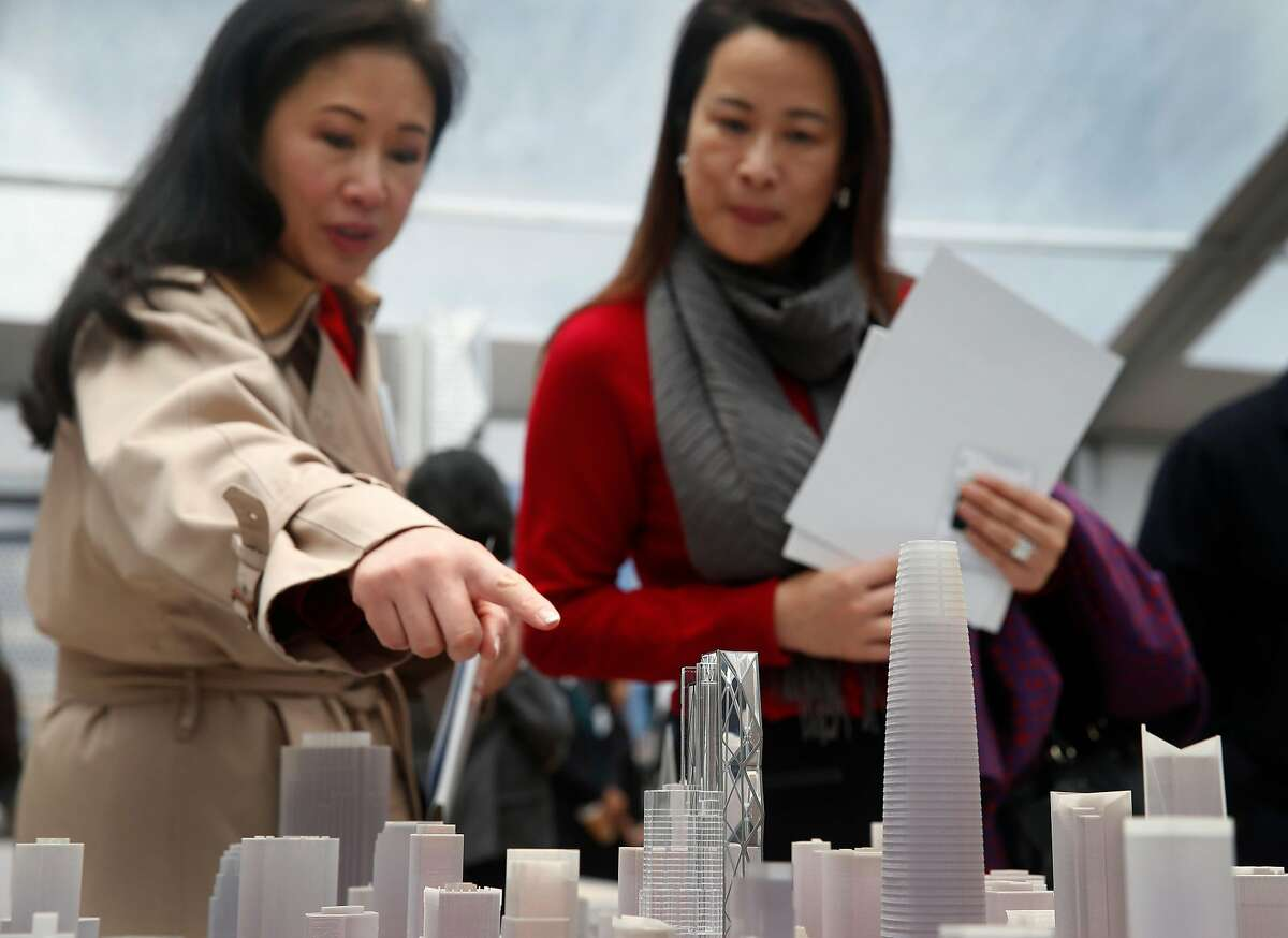 Jane Bachmann (left) and Maria Wang view a model depicting the 910-foot, 61-story Oceanwide Center, Salesforce Tower and their environs at a groundbreaking ceremony in San Francisco, Calif. on Thursday, Dec. 8, 2016. When completed in 2021, the residential and office tower on First Street will be the second tallest building in the city.
