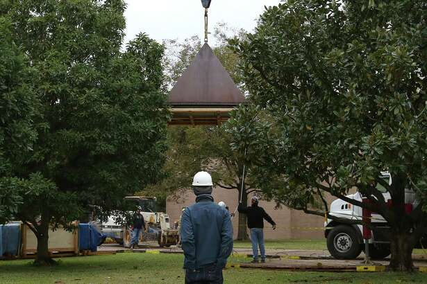 """Workers give instructions to a crane operator as they move Barnett Newman's monumental sculpture """"Broken Obelisk""""back to its home in the reflection pool at the Rothko Chapel on Tuesday, Dec. 8."""