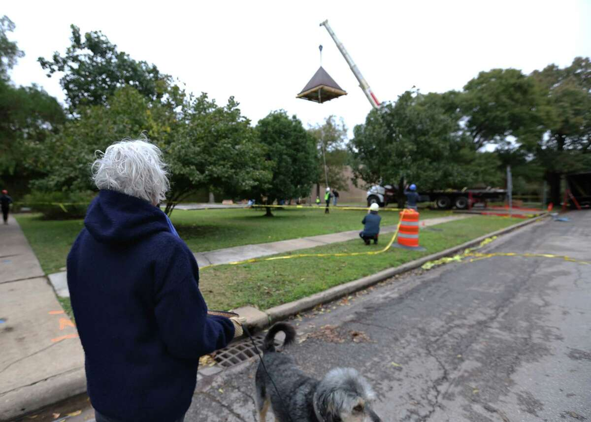 """Gerry Moohr stops with her dog, Crystal, to watch Barnett Newman's monumental sculpture """"Broken Obelisk"""" being returned to its home in the reflection pool at the Rothko Chapel Thursday, Dec. 8, 2016, in Houston. Moohr, who lives near by and walks by the chapel twice a day with Crystal, said she has missed the sculpture terribly. ( Yi-Chin Lee / Houston Chronicle )"""