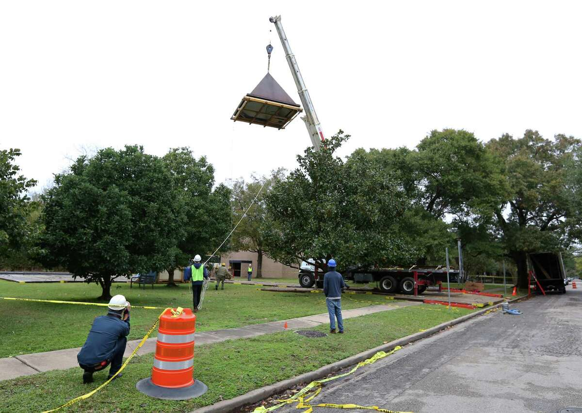 """Workers watch as Barnett Newman's monumental sculpture """"Broken Obelisk,"""" which was sent away to be restored earlier this year, is returned to its home in the reflection pool at the Rothko Chapel Thursday, Dec. 8, 2016, in Houston. ( Yi-Chin Lee / Houston Chronicle )"""
