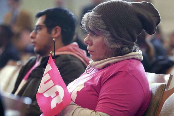 Left driver Elsa Gomez wears a pink shirt and holds a pink flag with the company's logo Thursday, Dec. 8, 2016 at city council chambers before the council voted 9-2 to approve contracts for transportation-network companies such as Uber and Lyft, which will continue operations in San Antonio.