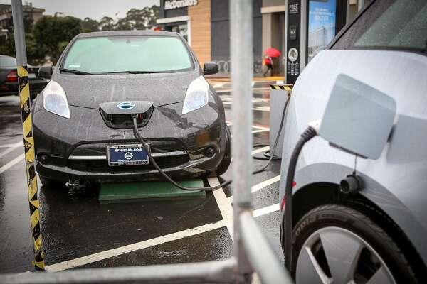 Two electric cars use up the two public charging stations in the Stonestown Galleria parking lot on Thursday, December 8, 2016 in San Francisco, Calif.