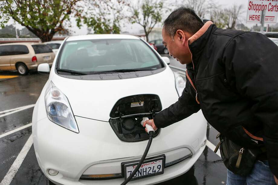 Joe Quan plugs in his electric car in one of the two public charging stations in the Stonestown Galleria parking lot in San Francisco. For those who want to charge at home or work, Pacific Gas & Electric plans to install 7,500 chargers at apartment buildings, condominiums and workplaces across Northern and Central California. Photo: Amy Osborne, Special To The Chronicle