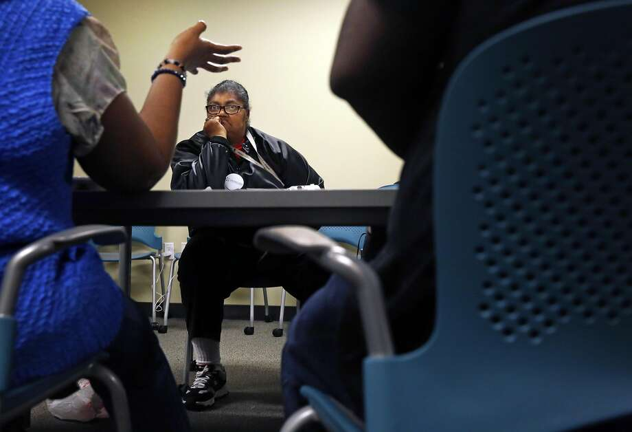 Anita Schools, who says she is most troubled by finances, listens to an HIV-positive woman speak about her experiences and fears at an Oakland support group that Schools organized. Photo: Leah Millis, The Chronicle