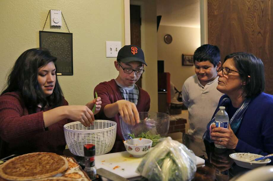 Patti Radigan (righ) instructs daughter Angelica and Angelica's boyfriend, Jayson Cabanas, on preparing green beans for Thanksgiving while Roman Tom Pierce, 8, watches. Photo: Leah Millis, The Chronicle