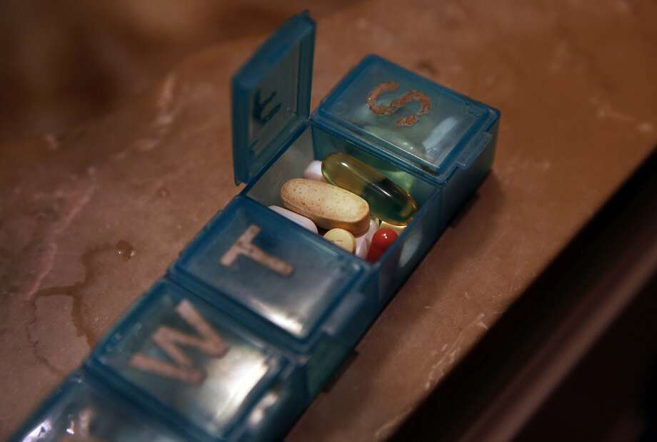 Daily HIV pills along with various vitamins and other drugs to treat ailments sit on a counter in a patient's San Francisco home. Photo: Leah Millis, The Chronicle