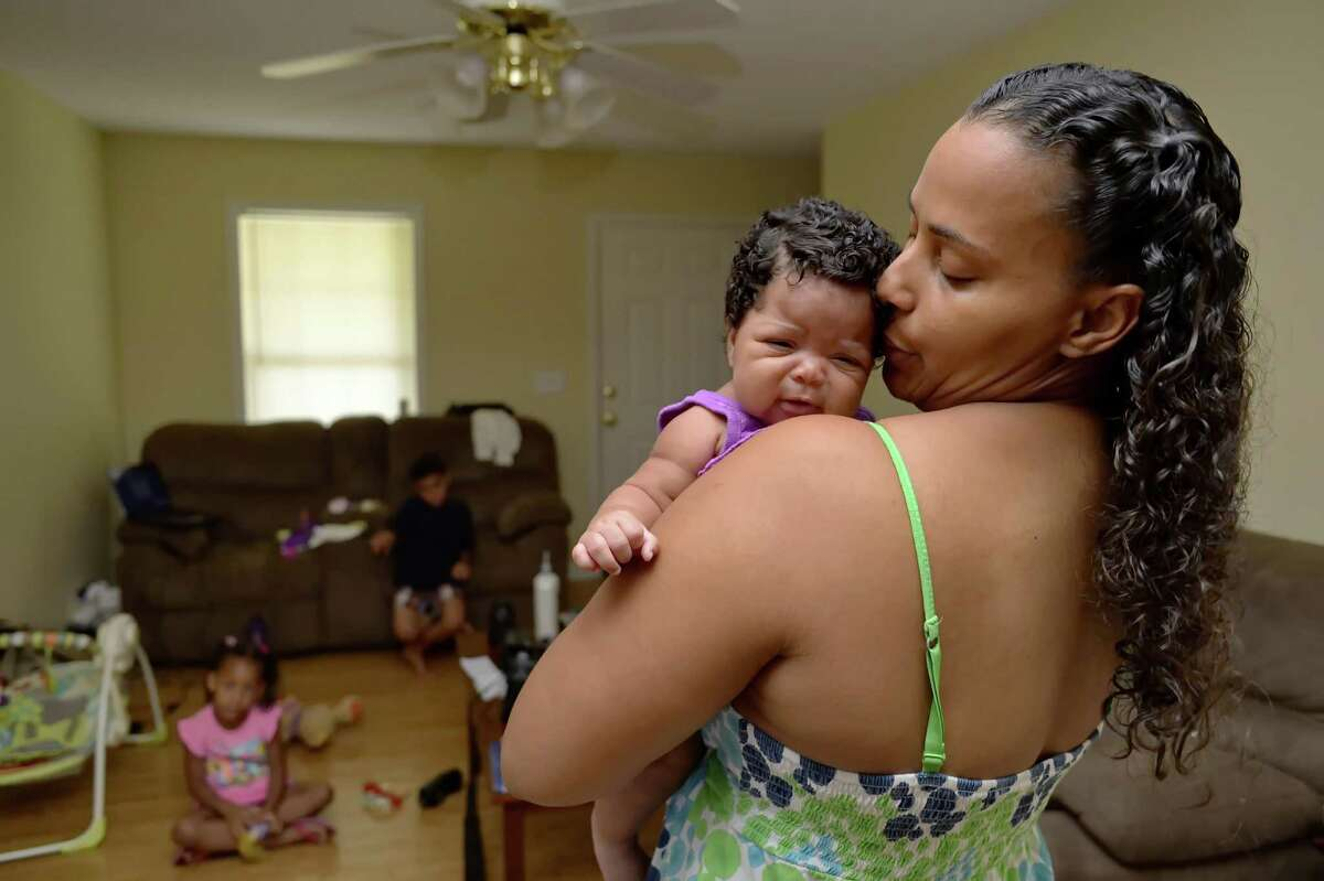 In this June 18, 2014 photo, Army Sgt. LaQuisha Gallmon holds her 2-month-old Abbagayl, as her children Dallin, 8, and Angelicah, 5, sit in their home in Greenville, S.C. Gallmon said that her local VA office had authorized her to see a private physician during her pregnancy, so she went to an emergency room after experiencing complications in her sixth month of pregnancy. She said the VA has thus far refused to pay the resulting $700 bill. (AP Photo/ Richard Shiro)