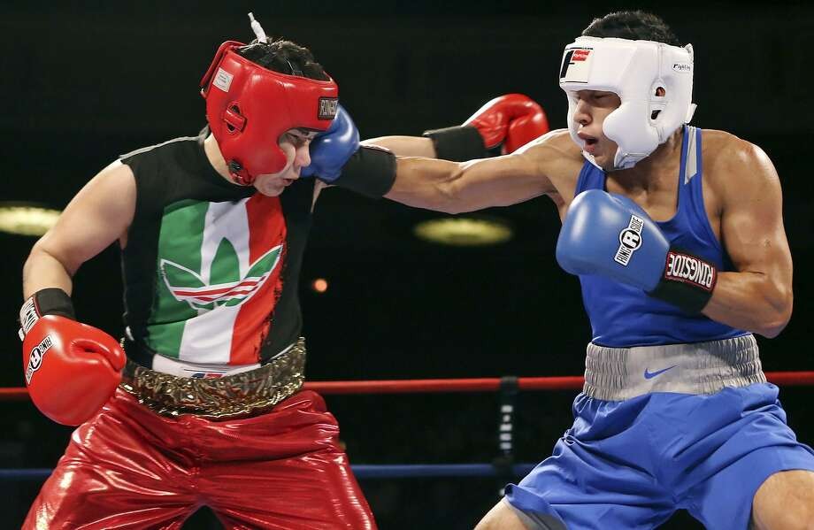 Jesse Rivera (left) is hit by Joshua Moreno during their open welterweight championship bout part of the 2015 San Antonio Regional Golden Gloves boxing tournament finals Feb. 21, 2015 at the Scottish Rite Auditorium. Moreno won by a unanimous decision. Photo: Edward A. Ornelas /San Antonio Express-News / © 2015 San Antonio Express-News
