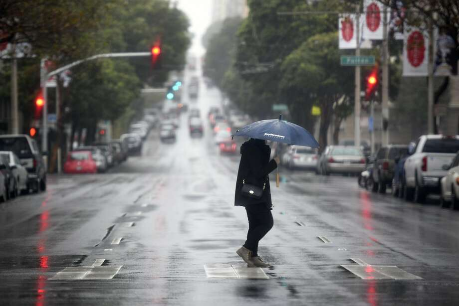 A woman walks across Franklin Street during a rain storm in San Francisco, CA, on Thursday, December 8, 2016. Photo: Michael Short, Special To The Chronicle