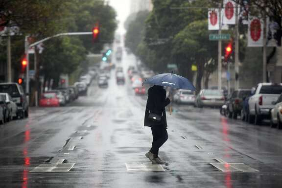 A woman walks across Franklin Street during a rain storm in San Francisco, CA, on Thursday, December 8, 2016.